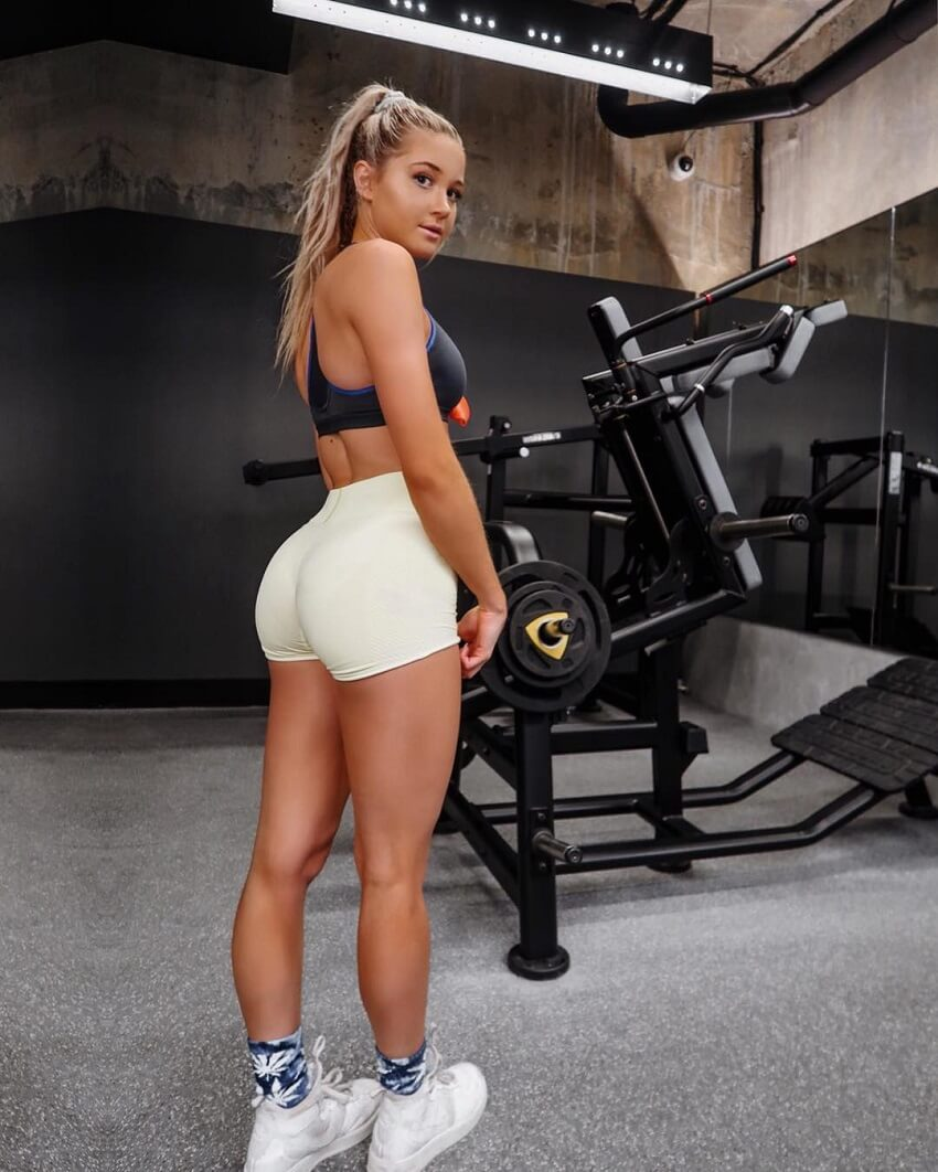 Lily Bowman standing by a leg press machine looking curvy and fit