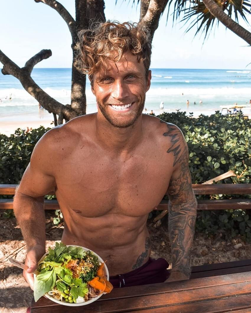 Matt Fox sitting shirtless in the shade near a beach, showing off his plate with vegan food
