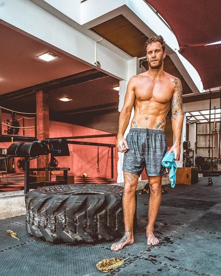 Matt Fox posing shirtless big a big tyre