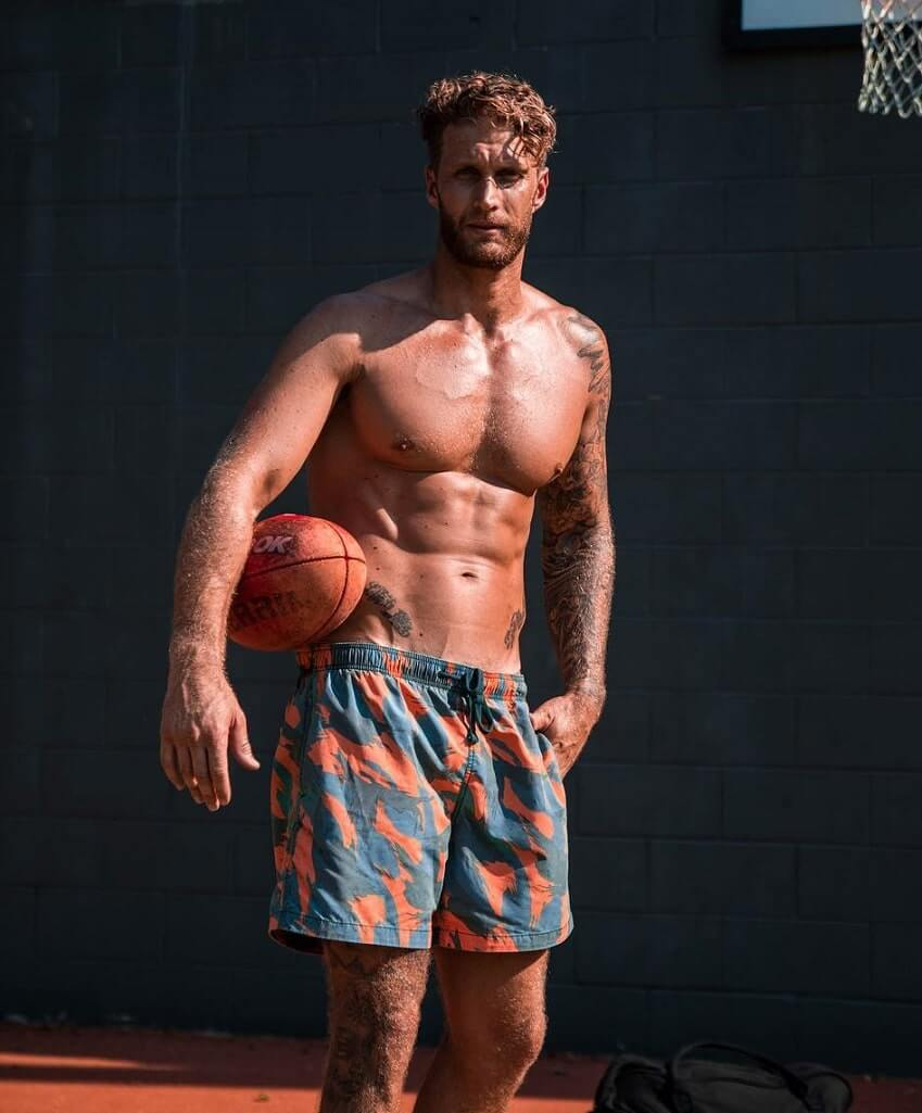 Matt Fox standing shirtless in the sun with a basket ball in his hand, looking muscular and ripped