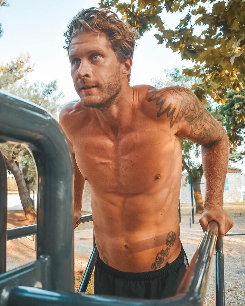 Matt Fox doing dips shirtless, looking strong and fit