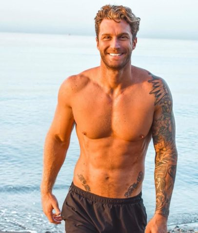 Matt Fox standing shirtless on the beach smiling for the photo, looking fit and lean