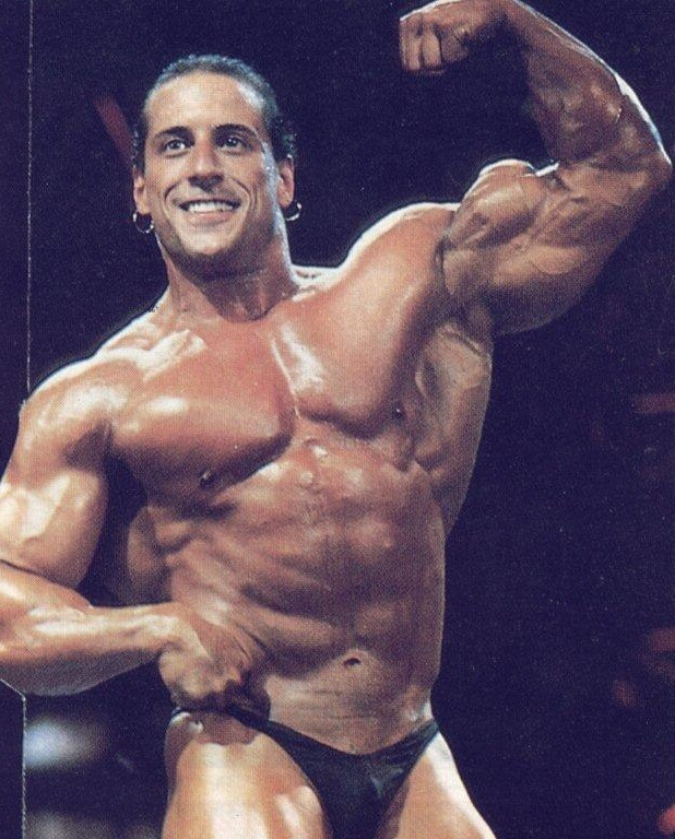 Mike Quinn flexing his biceps on the bodybuilding stage