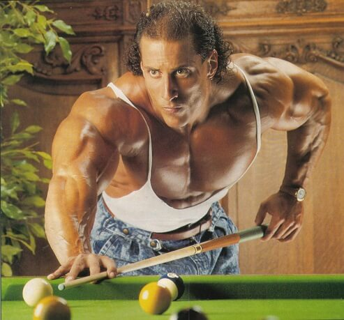 Mike Quinn playing pool in a white tank top looking huge