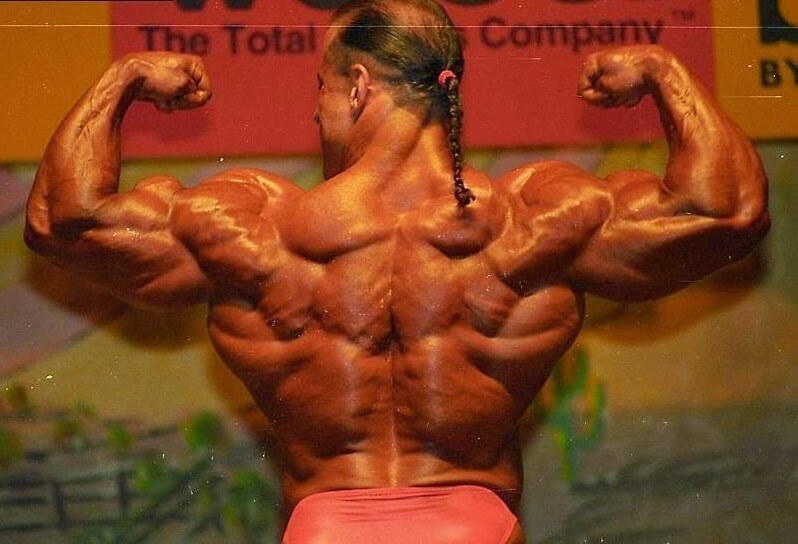 Mike Quinn flexing his back and arm muscles on the bodybuilding stage