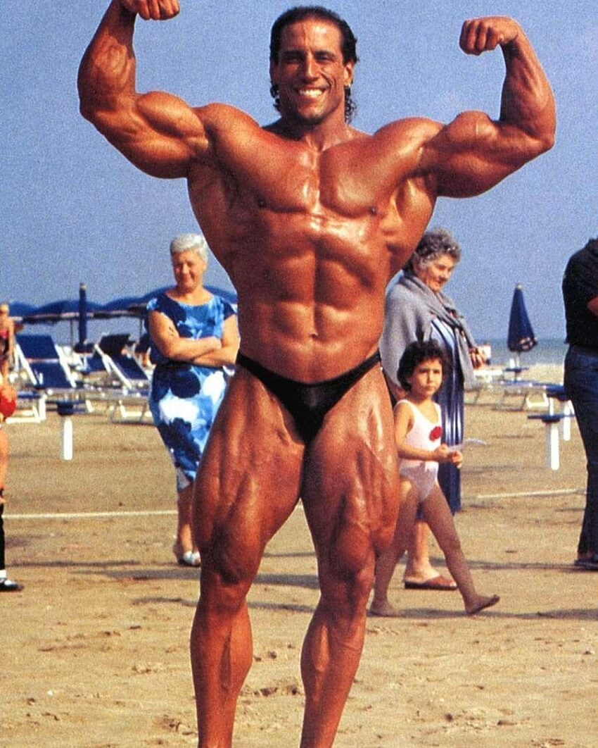 Mike Quinn doing a shirtless front double biceps flex on the beach, looking huge and ripped