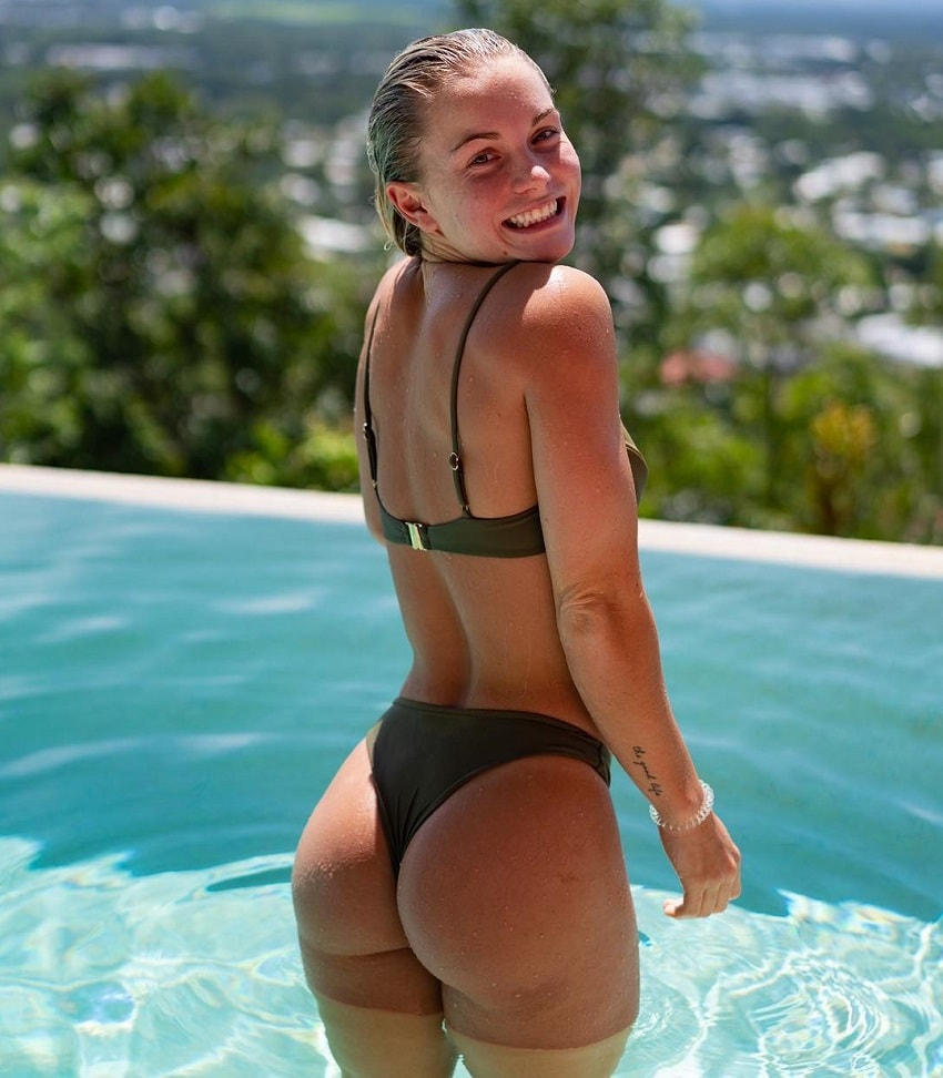 Morgan Rose Moroney posing in the pool, smiling, and showing off her incredible curvy glutes