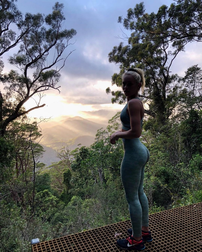Morgan Rose Moroney standing on the mountain peak among trees and green lush nature, watching a misty sunrise