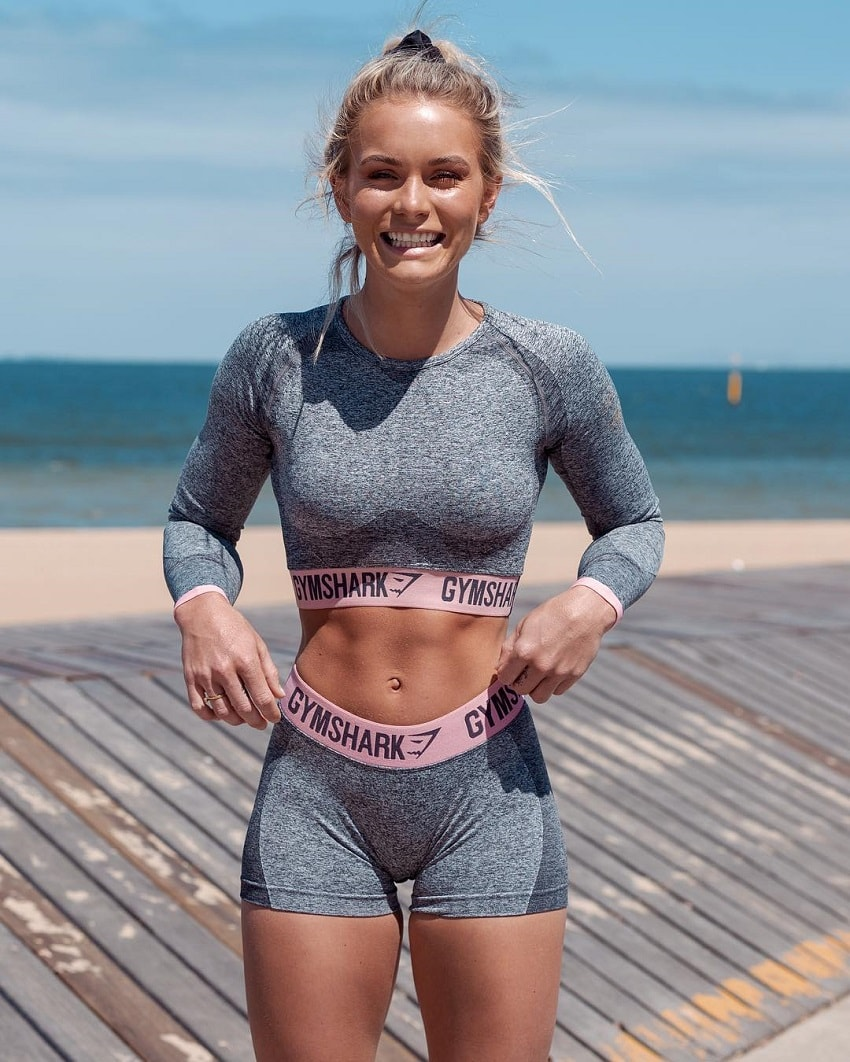 Morgan Rose Moroney smiling for the photo wearing her workout clothes on a sunny day near a beach