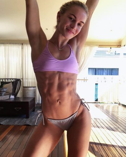 Morgan Rose Moroney stretching her arms up and smiling at the camera, her abs looking ripped and strong