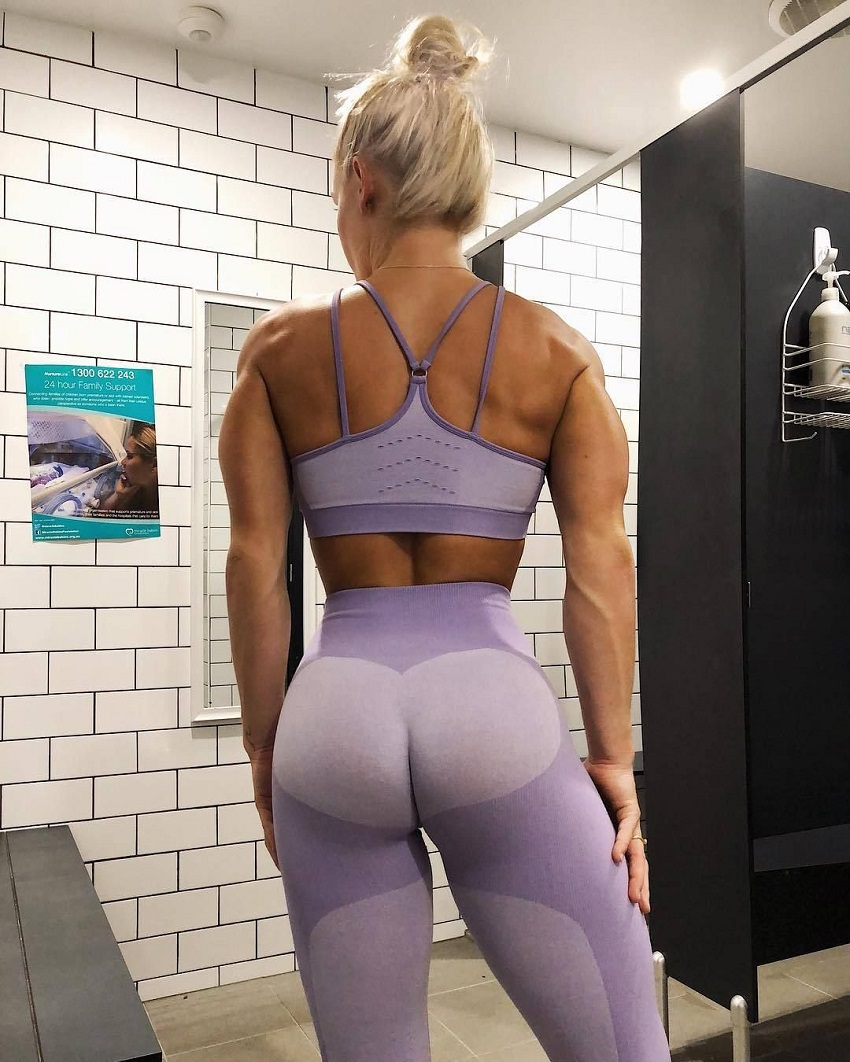 Morgan Rose Moroney posing in the gym locker room, showing off her muscular back and curvy glutes in leggings