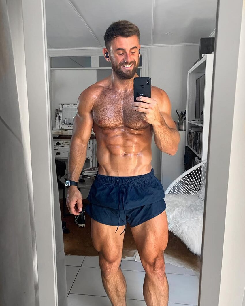 Nathan McCallum taking a picture of himself shirtless in the mirror, looking strong and ripped