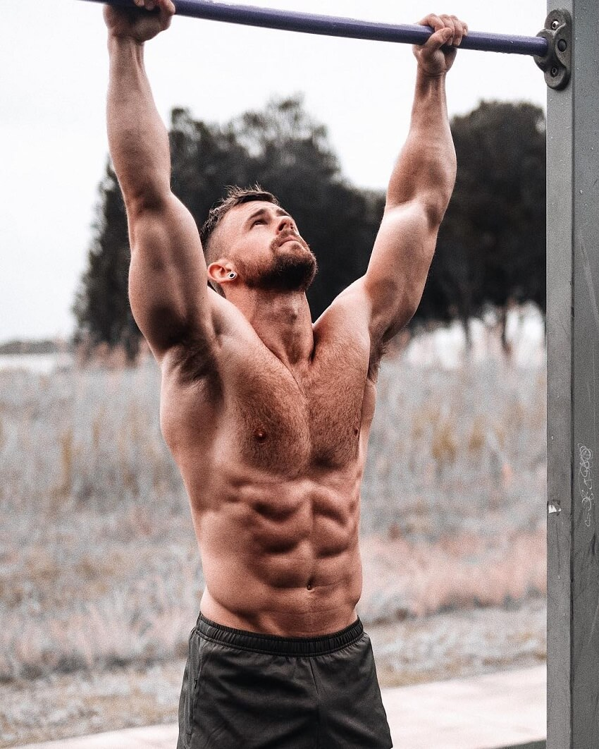 Nathan McCallum reaching for a pull-up bar with his hands while being shirtless, looking ripped and muscular