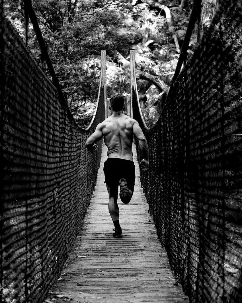 Nathan McCallum running shirtless across a bridge, looking fit and ripped