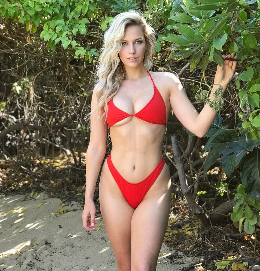 Paige Spiranac posing outdoors in nature wearing a red bikini, looking curvy and toned