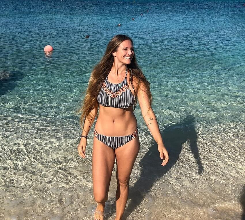 Rachel Brathen walking in shallow sea waters, looking fit and healthy