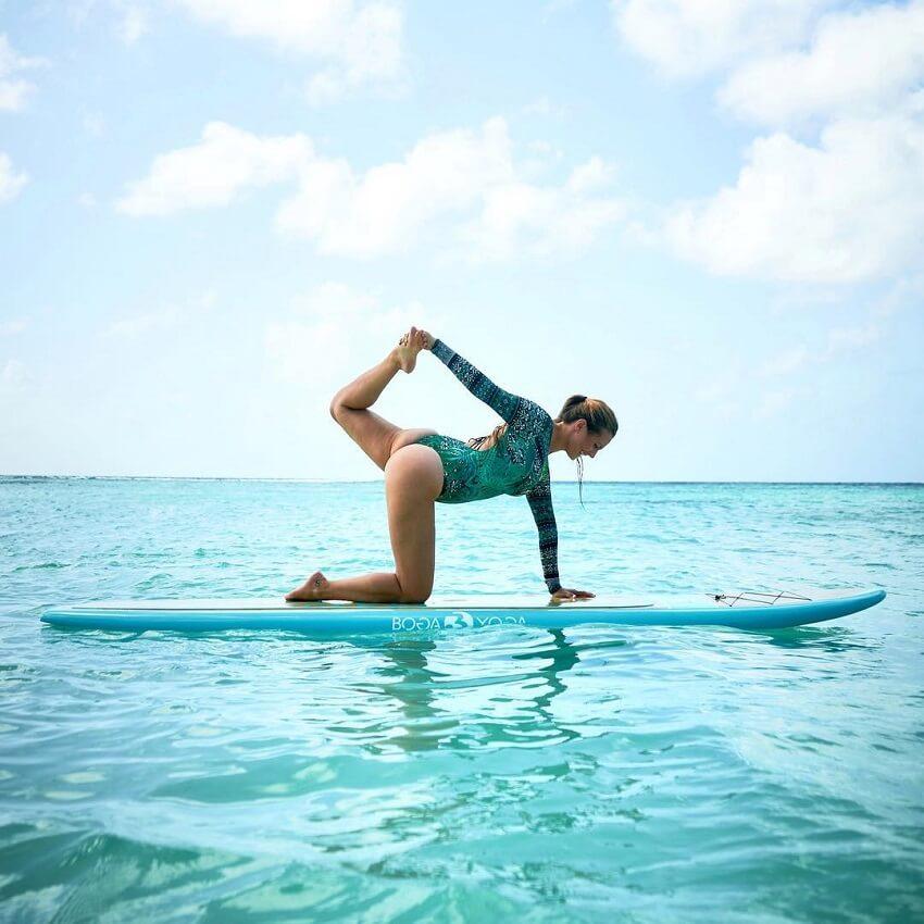 Rachel Brathen doing yoga on a surfboard
