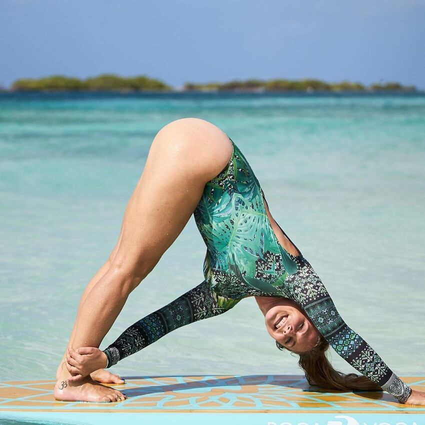 Rachel Brathen performing yoga poses on a surf board