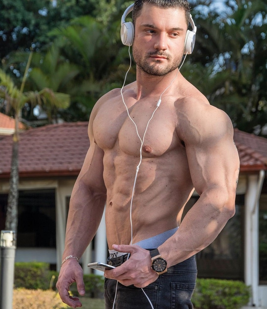 Rafael Rey standing shirtless outdoors with headphones on, looking swole and ripped