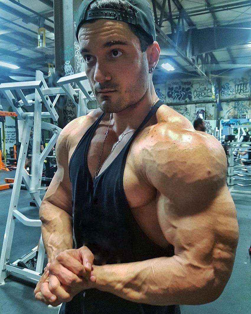 Rafael Rey flexing his vascular and builging shoulders in the gym