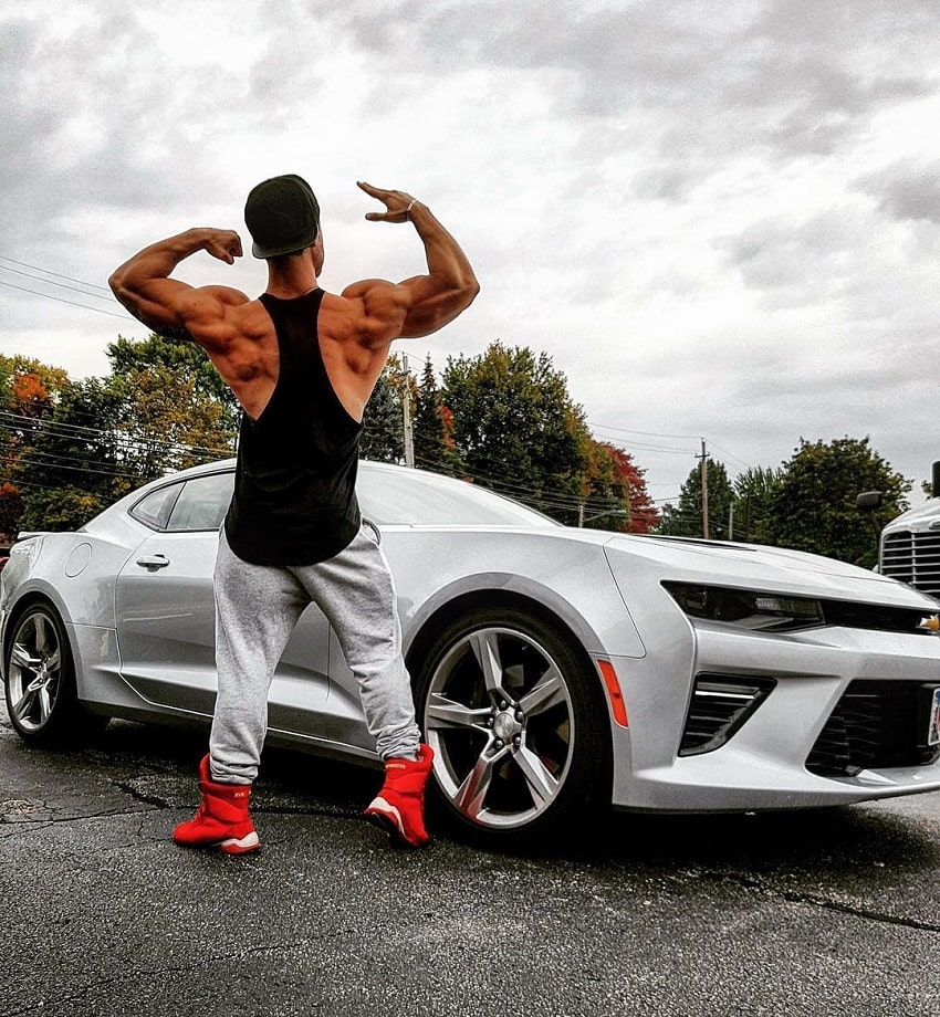 Rafael Rey standing by a new white sports car, flexing his back muscles