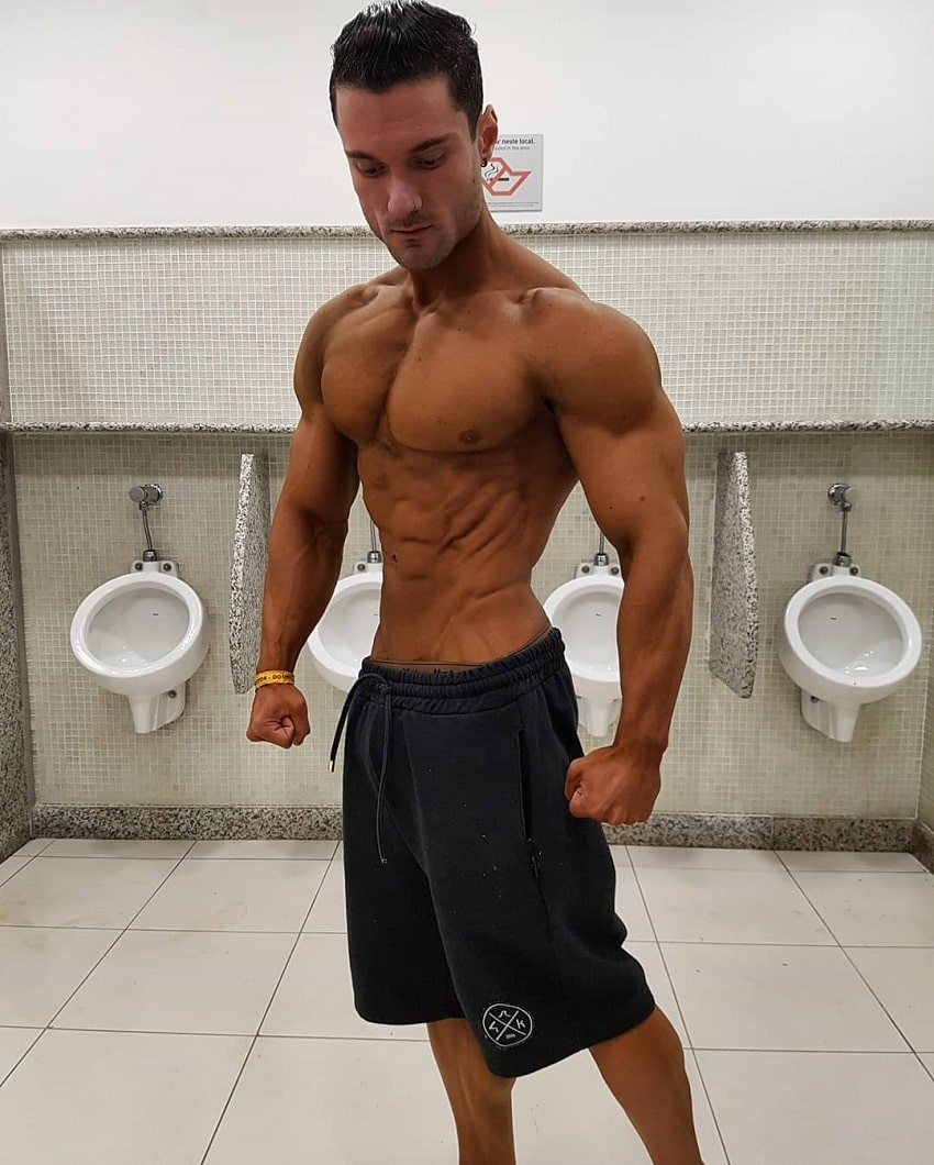 Rafael Rey standing shirtless in the bathroom looking tanned up and ripped