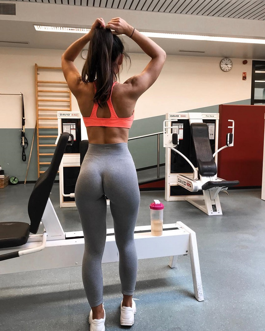 Sanna Maria standing in the gym tying her hair, wearing tight grey leggings which reveal her amazingly curvy glutes
