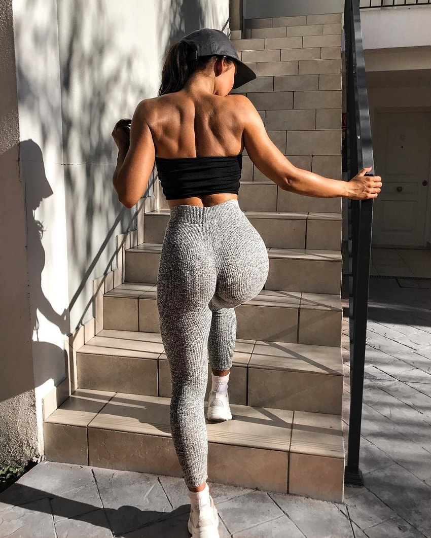 Sanna Maria walking up the stairs in her tight grey leggings, looking curvy and fit
