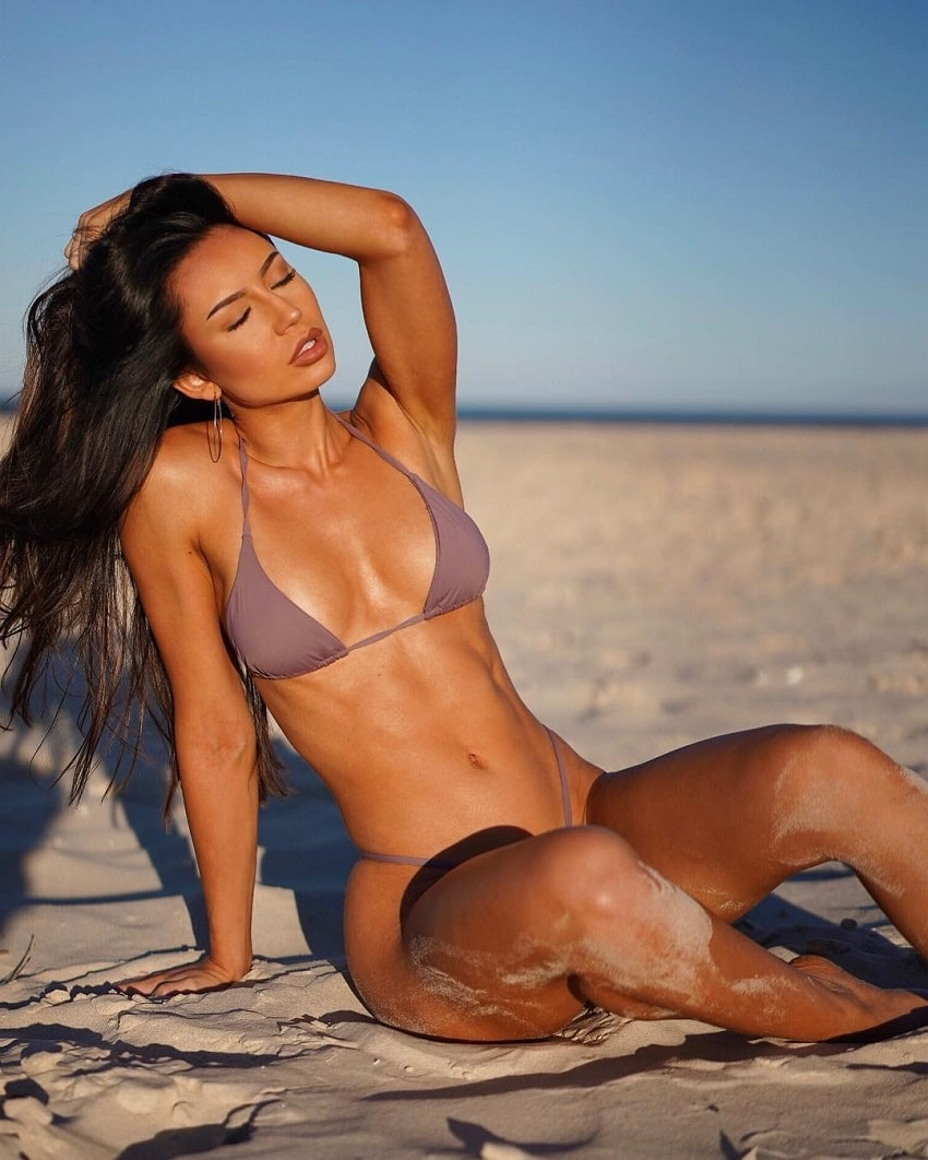Sanna Maria sitting on the sand beach soaking up last rays of the sun before a sunset, looking fit and lean