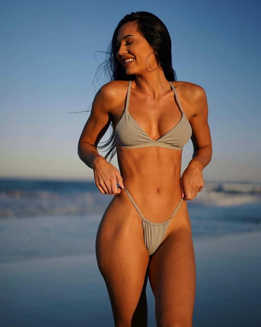 Sanna Maria standing on the shore during a sunset looking fit and lean