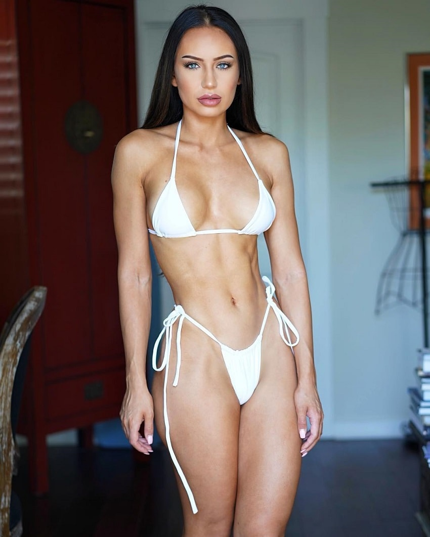 Sanna Maria posing in a revealing white bikini, looking fit and lean