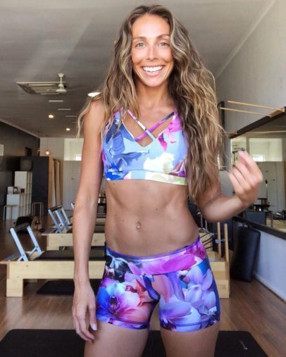 Sara Colquhoun posing for a photo in her colorful sports wear looking fit