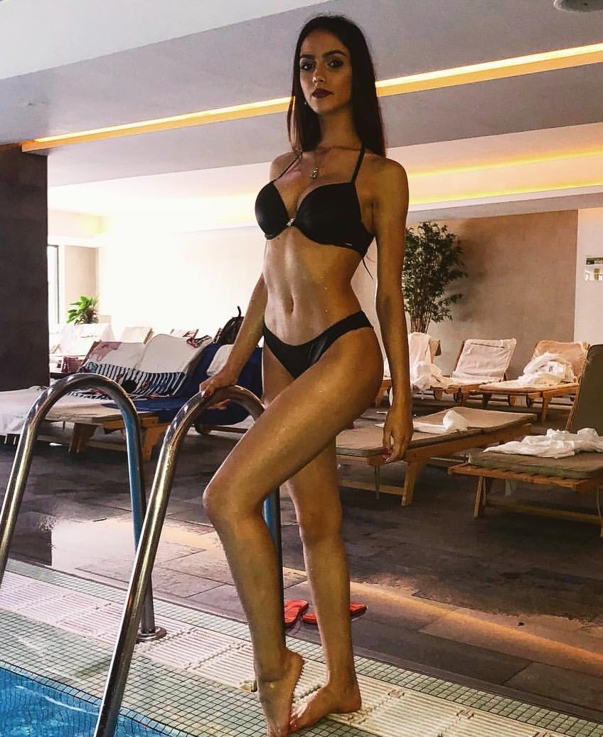 Sara Damnjanovic posing by the pool wearing a black bikini looking fit and lean