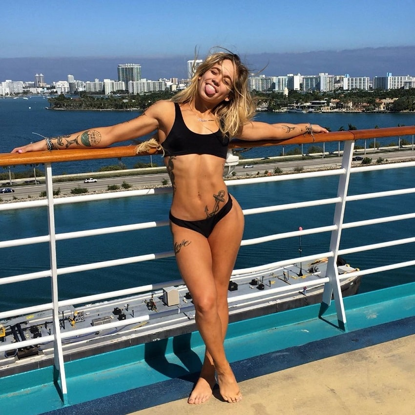 Skylar Stegner standing on the pier and smiling for the camera, looking fit and lean