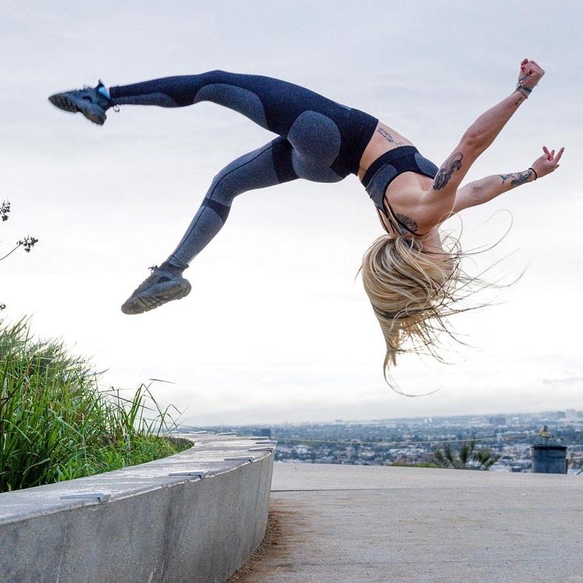 Skylar Stegner doing acrobatics outdoors on concrete near the sea
