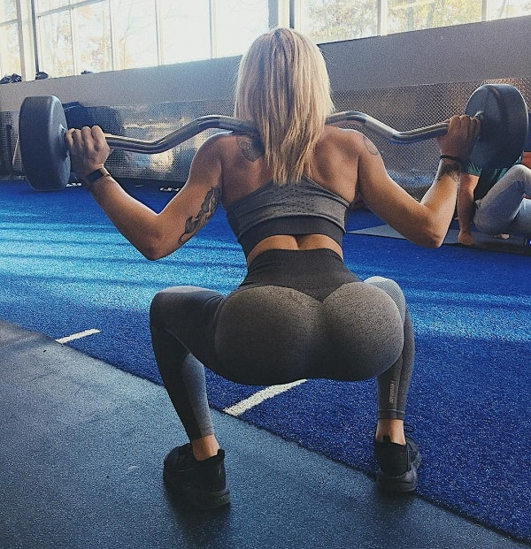 Skylar Stegner doing barbell squats in tight grey leggings showing her curvy glutes