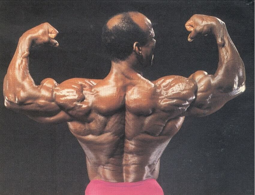 Albert Beckles flexing back double biceps, looking huge and ripped