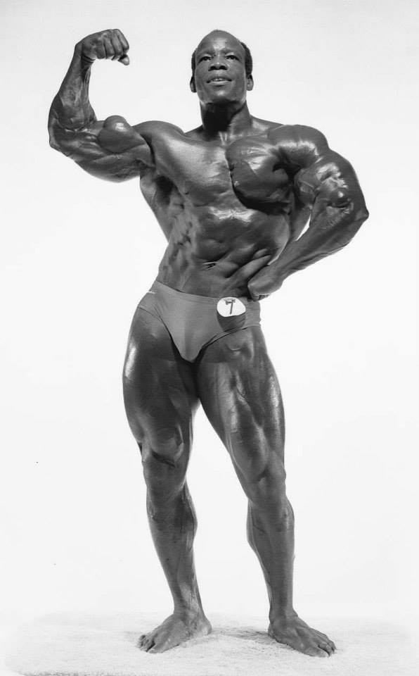 Albert Beckles flexing his biceps shirtless bodybuilding
