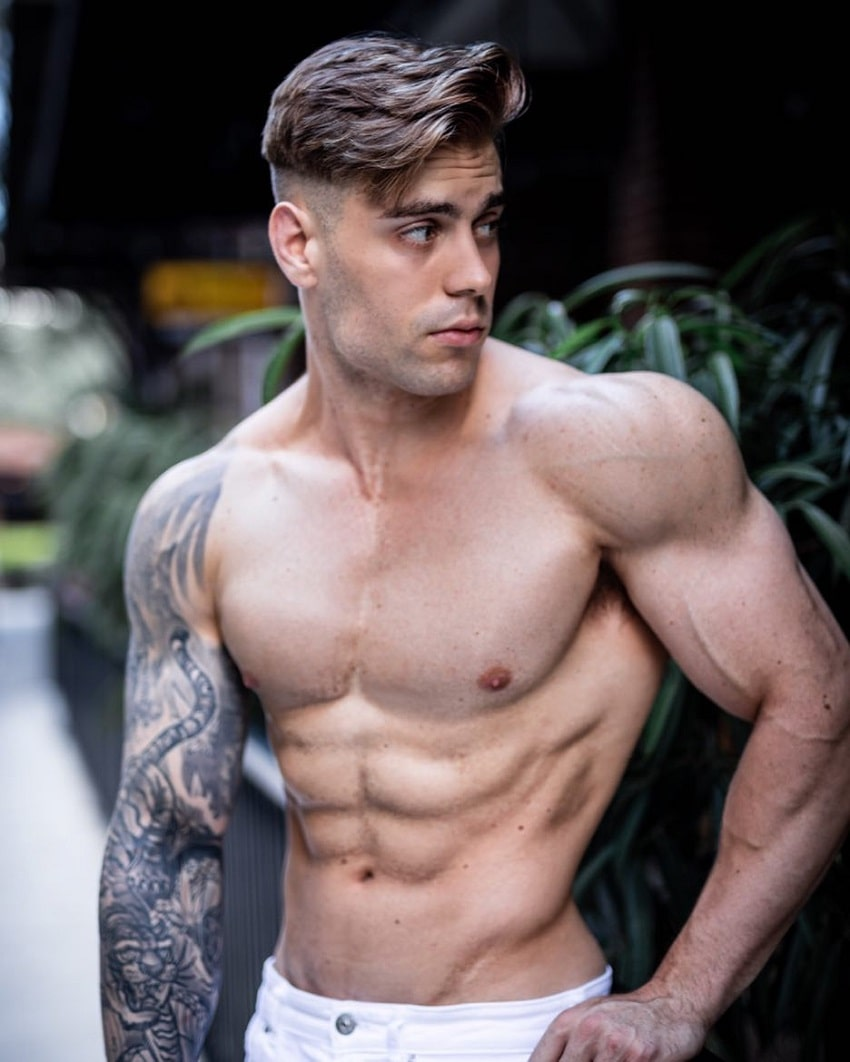 Andre Habowsky posing shirtless on the street, looking muscular and ripped