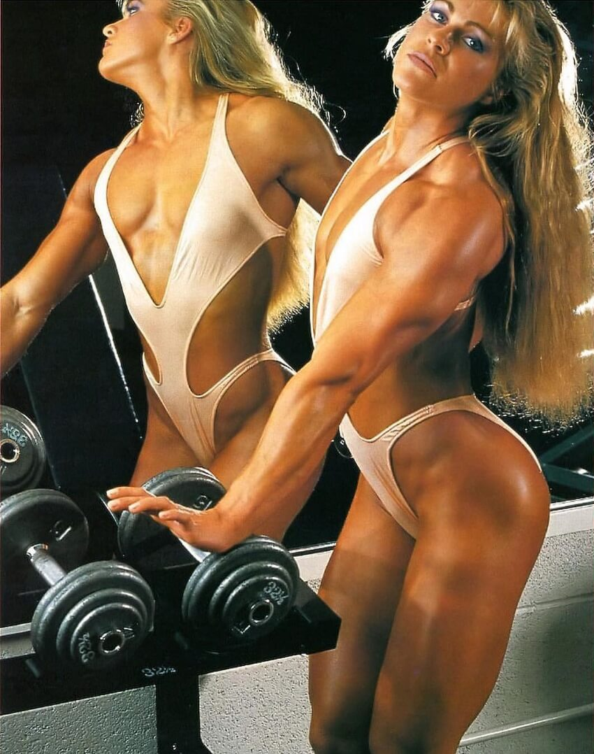 Anja Langer posing by the dumbbells in the gym