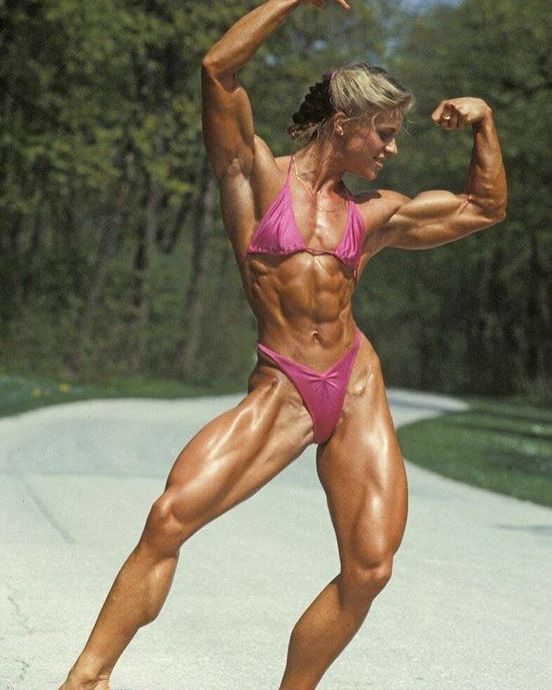 Anja Langer doing a front double biceps pose in a pink bikini
