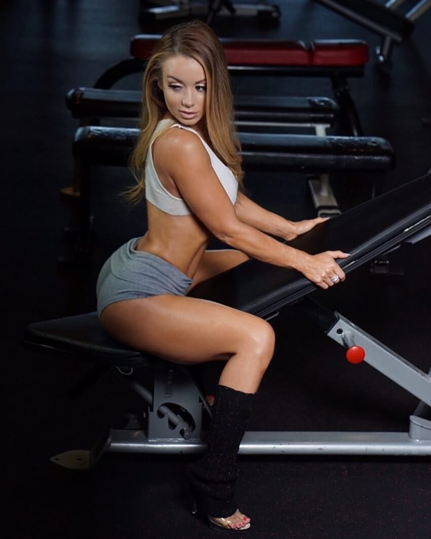 Annie Parker sitting on a bench in the gym posing for a photo shoot