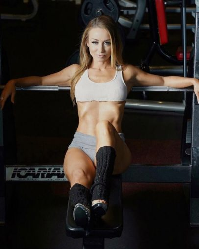 Annie Parker seated on a bench in the gym posing in a fitness photo shoot