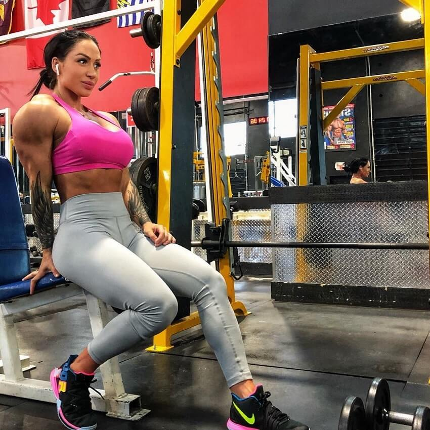 Azaria Glaim sitting on the bench in the gym, flexing her triceps