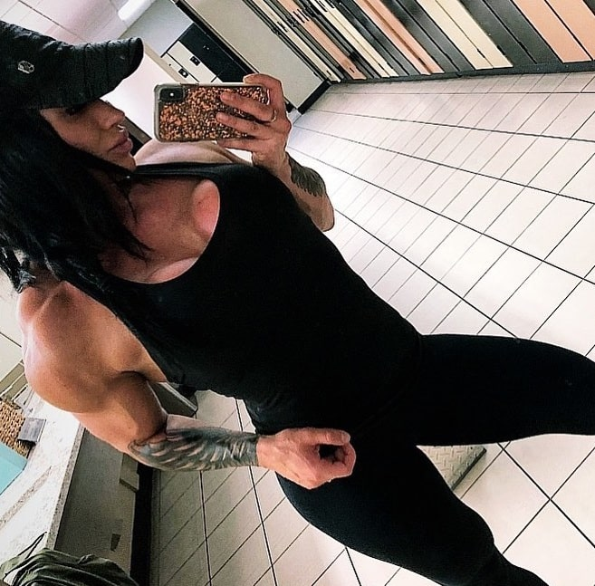 Azaria Glaim taking a selfie of her fit muscles in a bathroom