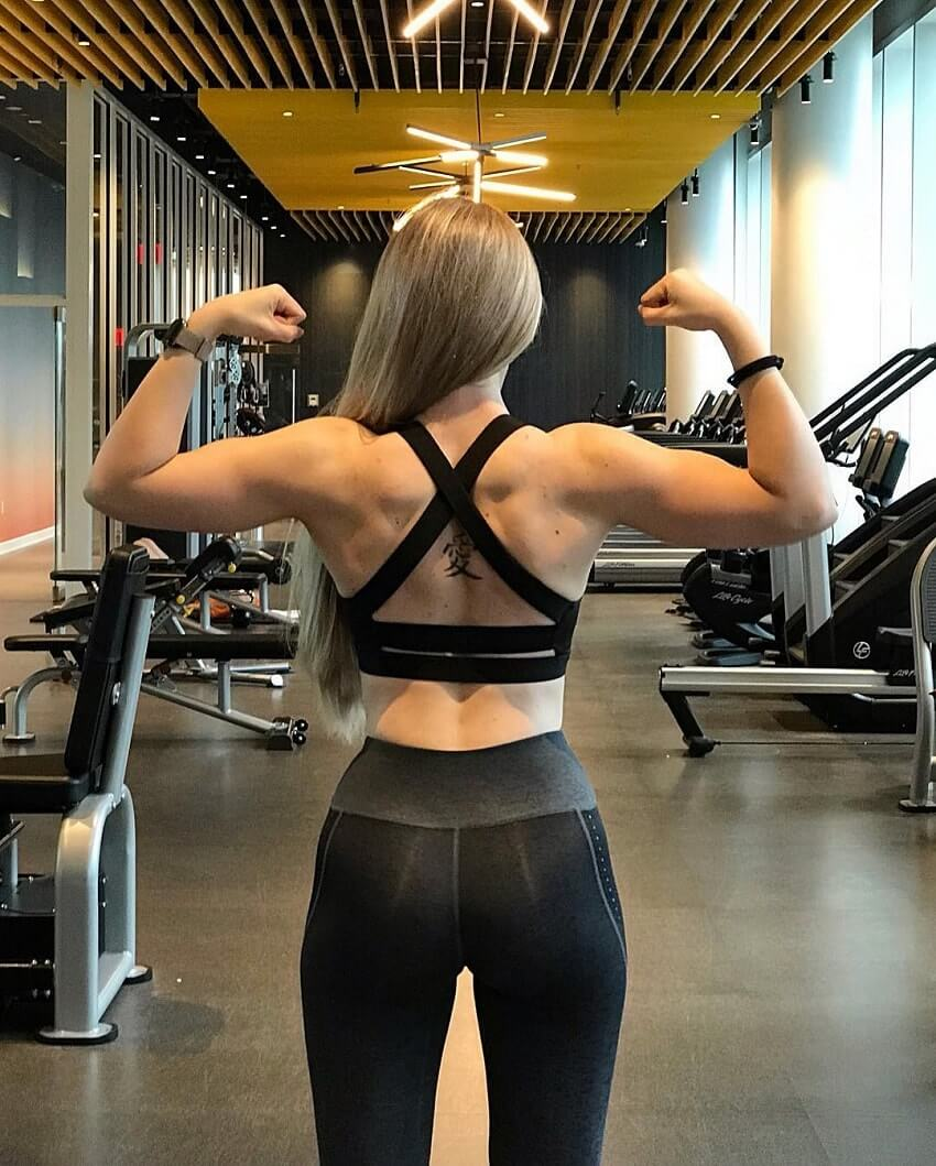 Bella Rahbek flexing her back and biceps in the gym
