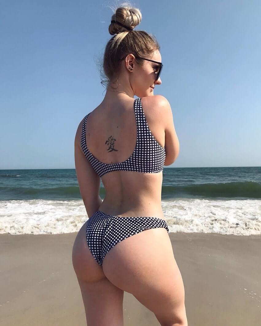 Bella Rahbek showcasing her glutes wearing a swimming suit on the beach