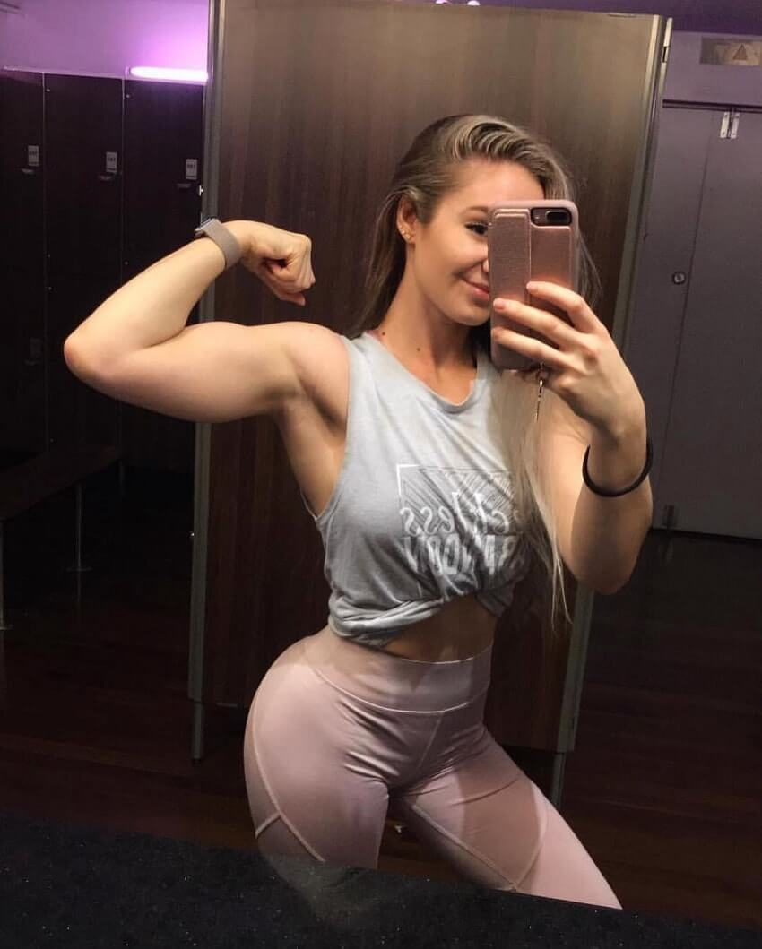 Bella Rahbek flexing her biceps in the gym selfie
