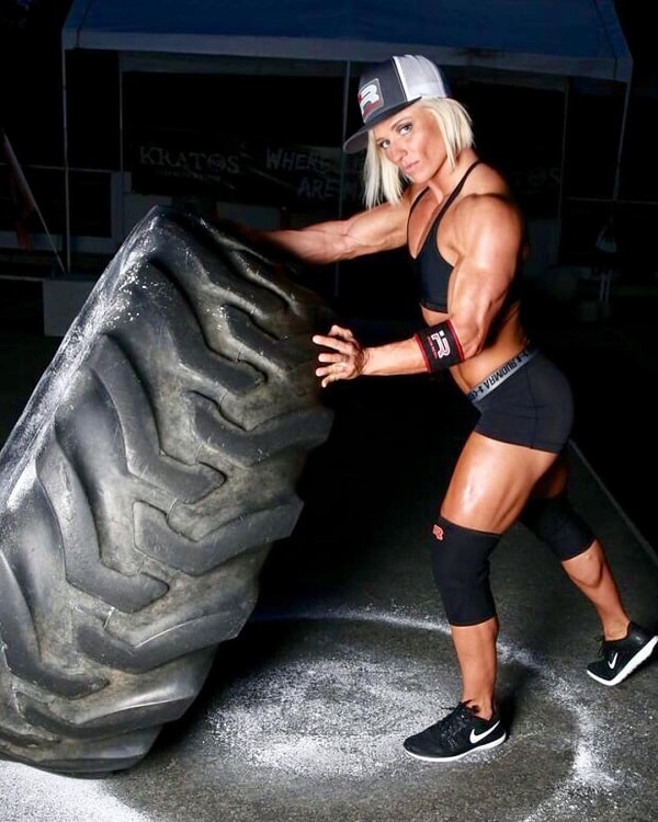 Brooke Walker lifting a heavy tire in a fitness photo shoot