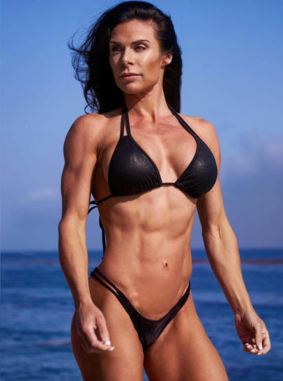 Camile Periat posing on the beach in a black bikini looking awesome and fit